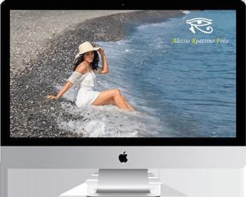 foto di una ragazza in spiaggia con vestito bianco e cappello vista dal monitor di un mac