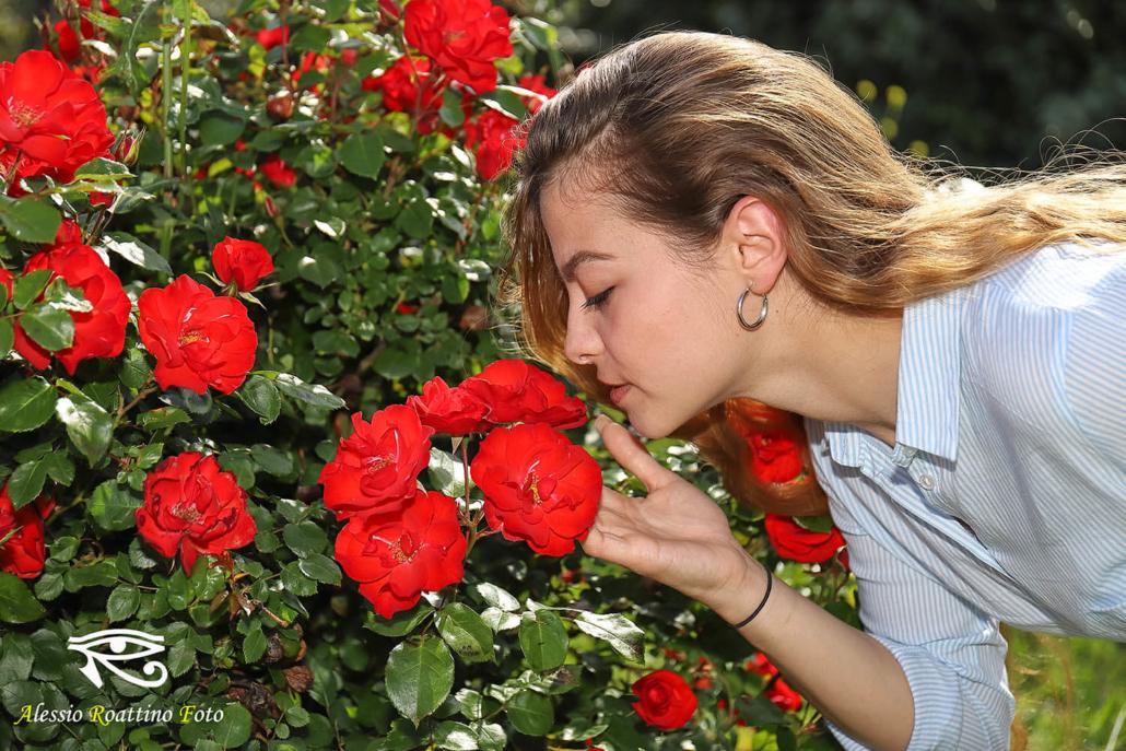 Adriana, ragazza bionda ripresa mentre sta annusando delle rose rosse