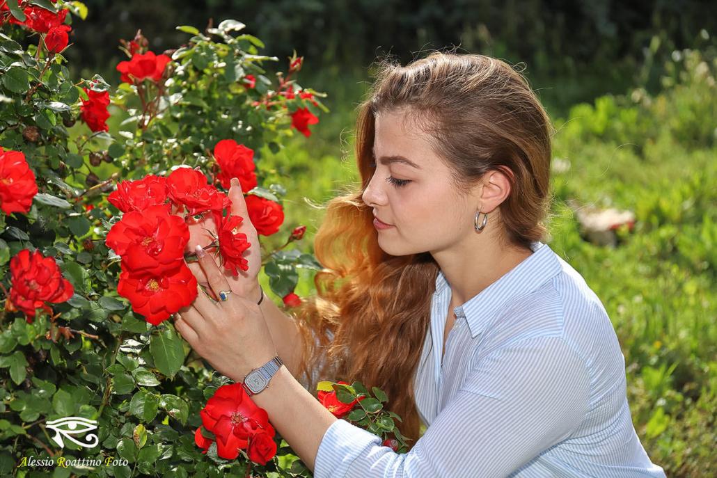 Adriana, ragazza bionda ripresa mentre sta osservando delle rose rosse