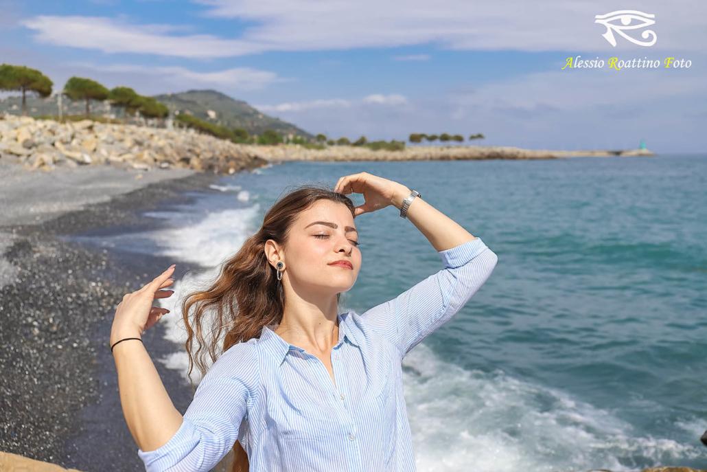 Adriana, ragazza in riva al mare mentre si aggiusta i capelli sotto i raggi del sole