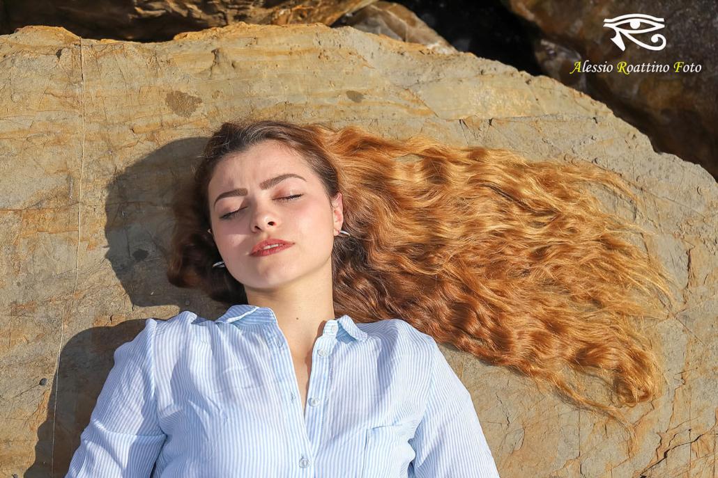 Adriana, ragazza ripresa in primo piano mentre è assopita sotto i raggi del sole con i capelli lunghi adagiati sullo scoglio a mo di bandiera