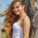 Adriana, ragazza vestita sportiva, appoggiata ad un albero mentre sorride
