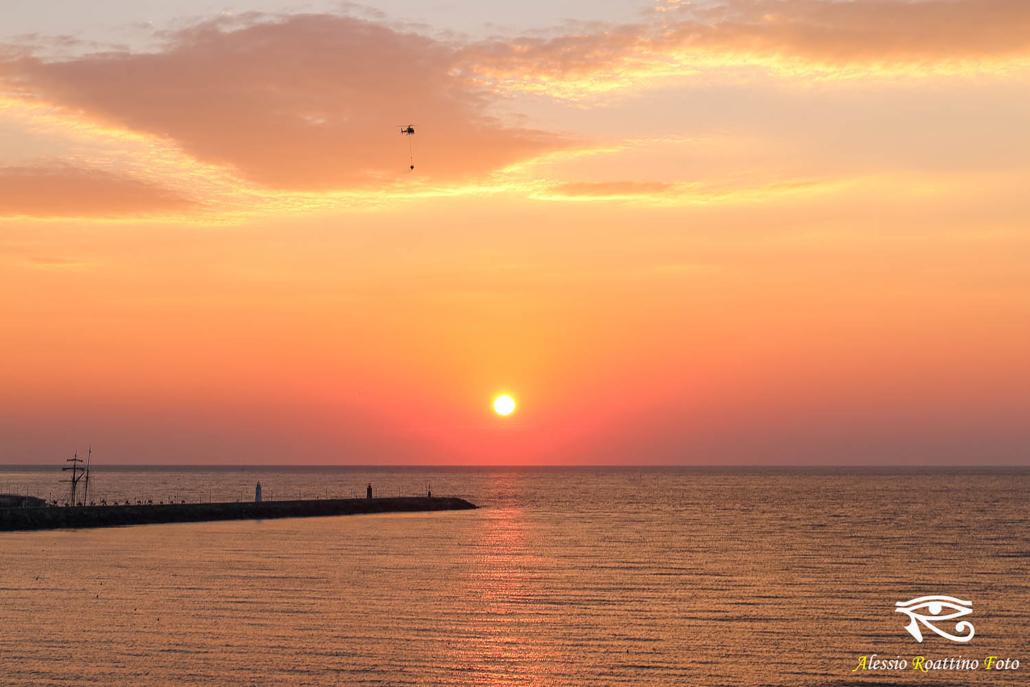 Alba sul molo lungo della marina di Porto Maurizio, mentre passa un elicottero antincendio