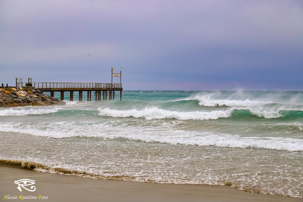 Albenga, onde spinte dal forte vento che si infrangono sulla spiaggia vicino al molo