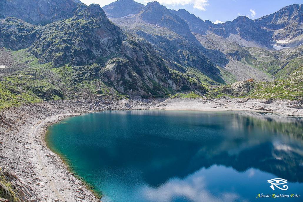 Entracque, lago del Chiotas con le montagne sullo sfondo e il cielo riflessi sull'acqua