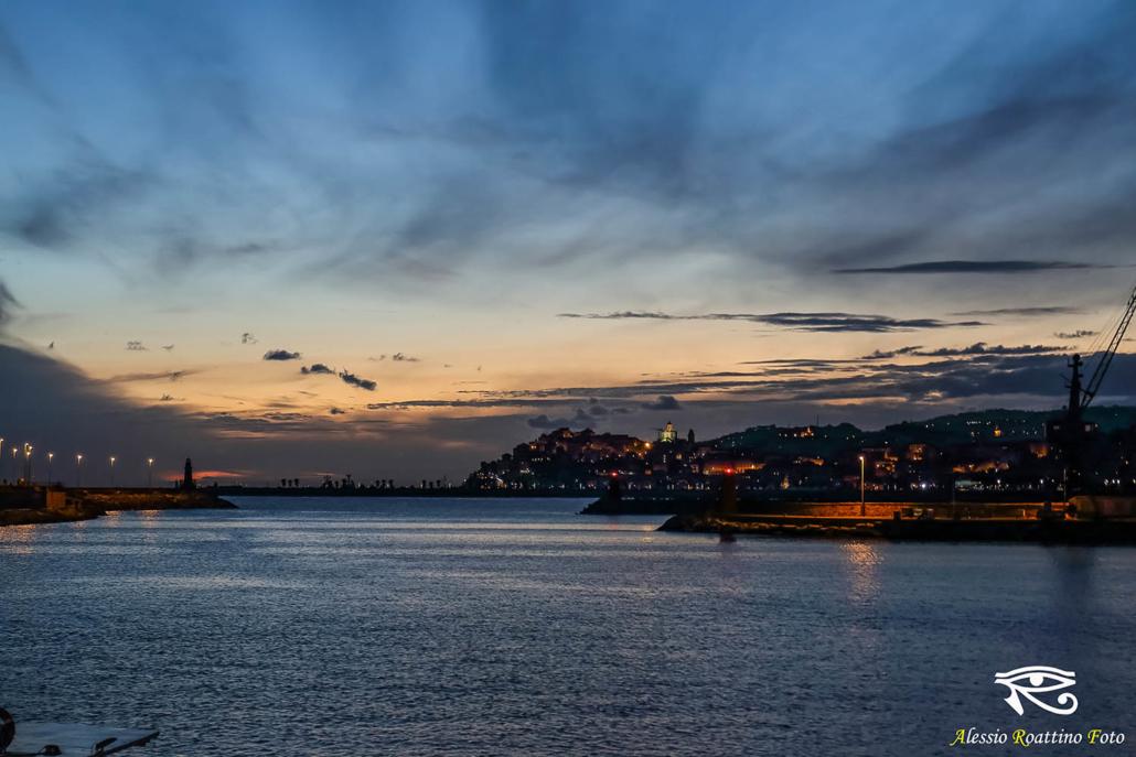 Imperia, l'entrata al porto di Oneglia con Porto Maurizio sullo sfondo nell'ora blu del tramonto