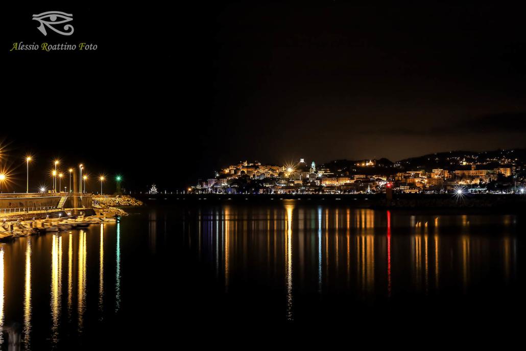 Imperia, l'ingresso del porto di Oneglia di notte con le luci che si riflettono sull'acqua