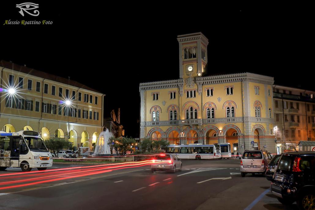 Imperia, piazza Dante ripresa di notte con le scie dei fari posteriori delle auto che passano