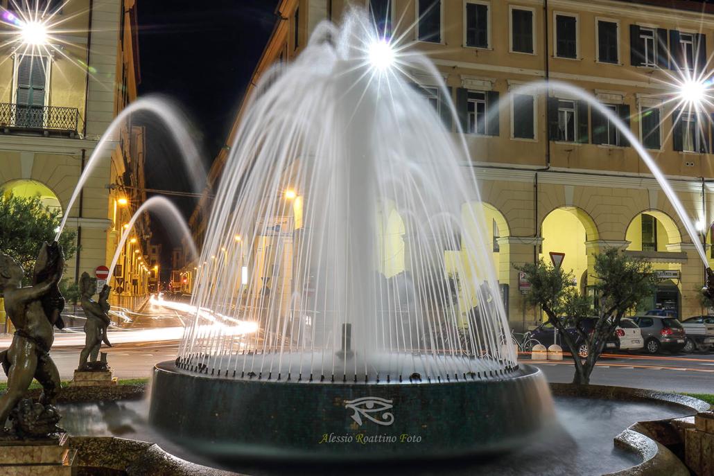 Imperia, ripresa notturna della fontana di piazza Dante in primo piano