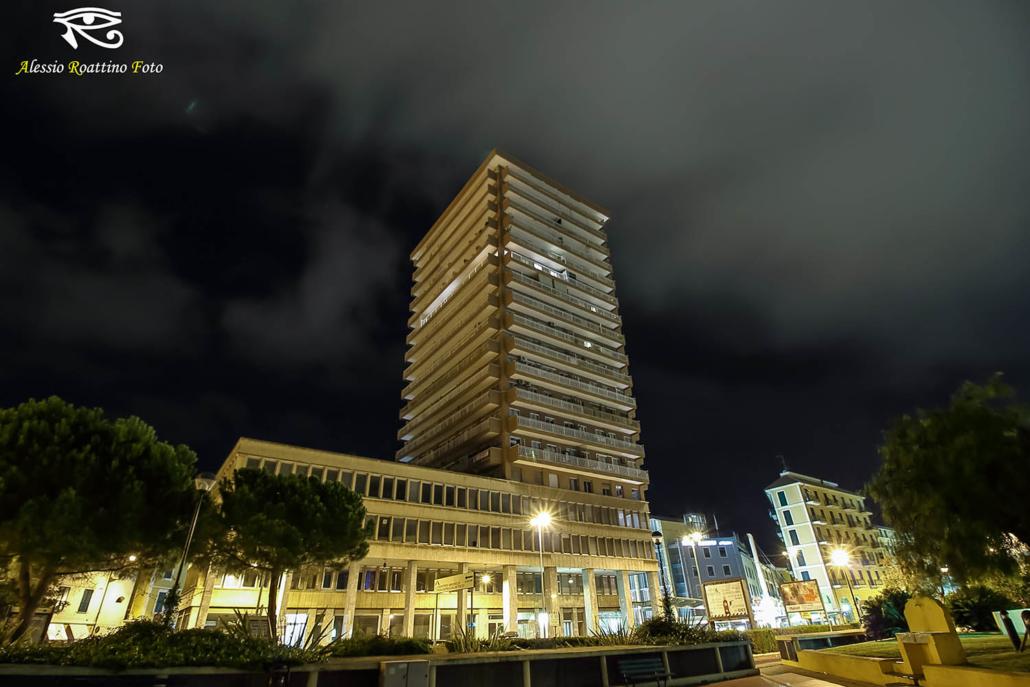 Imperia, vista notturna del grattacielo sovrastato da nuvole bianche