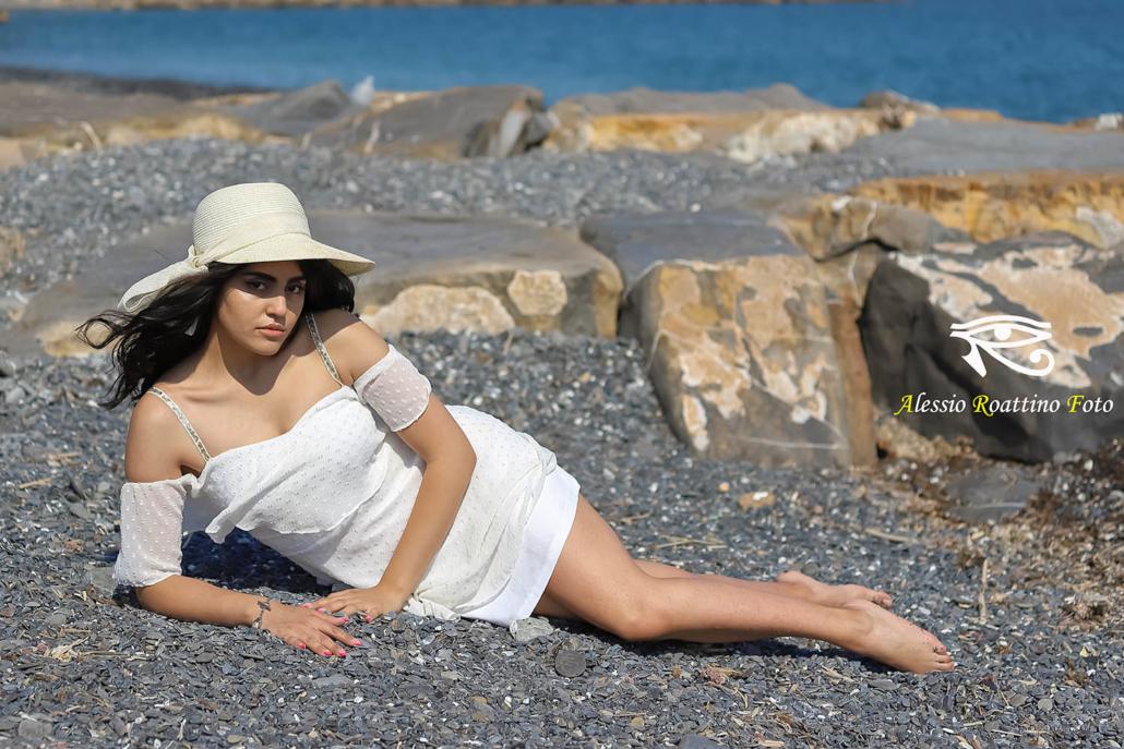 Kami, modella in abito bianco e cappello sdraiata di fianco sulla spiaggia del parco urbano di Imperia