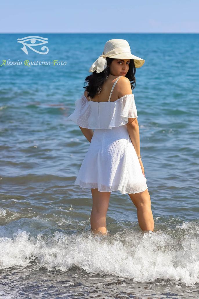 Kami modella in abito bianco sulla spiaggia con i pieni in acqua col passaggio di un onda ad Imperia
