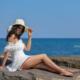 Kami modella con vestito bianco e capello seduta su uno scoglio vicino al mare in posa sexy ad Imperia