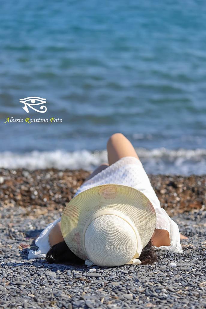 Kami modella con cappello sdraiata in spiaggia