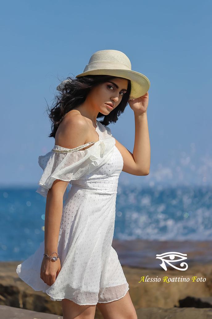 Kami modella in abito bianco mosso dal vento e cappello in riva al mare con onda sullo sfondo