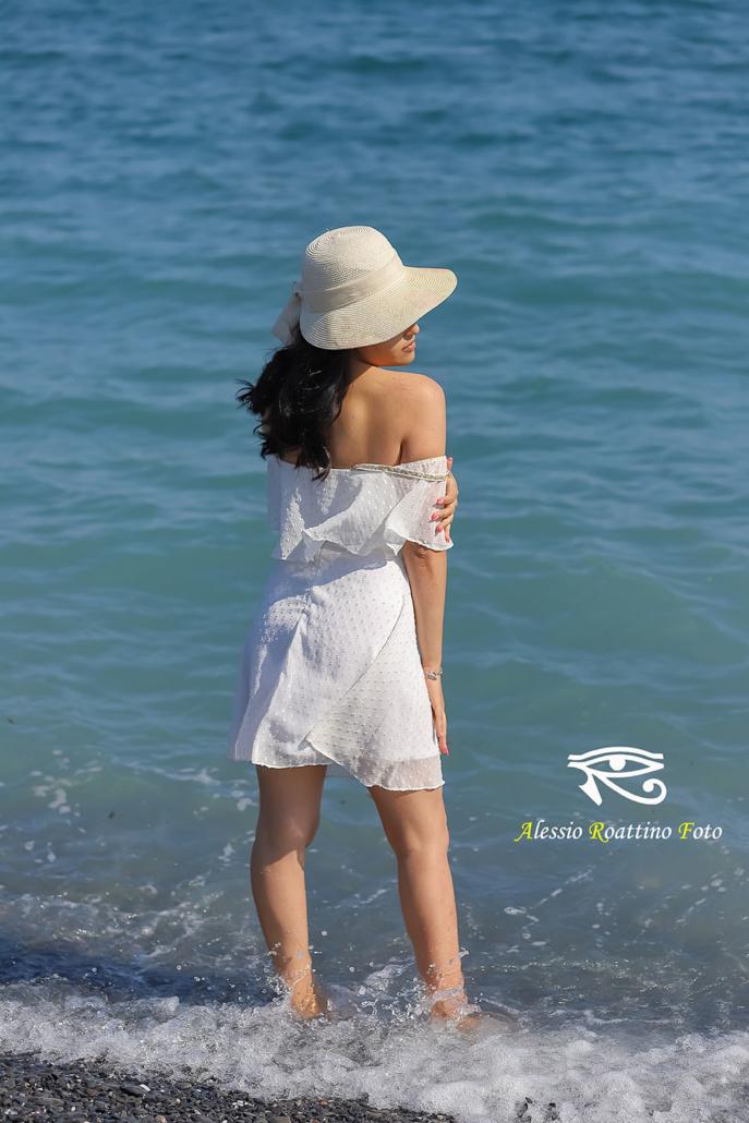Kami, modella in spiaggia con piedi in acqua mentre si accarezza un braccio