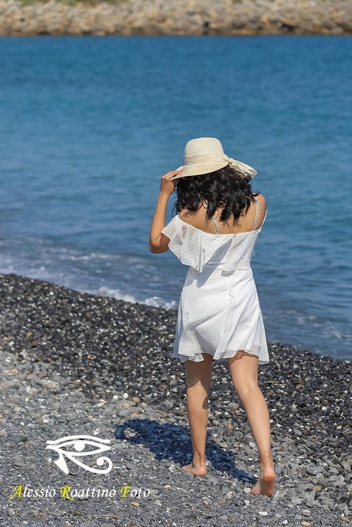 Kami, modella in abito bianco mentre passeggiata sulla spiaggia al parco urbano a Imperia