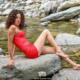 Nadia, modella con abito rosso seduta, senza scarpe, sulla pietra nel letto del fiume a Ormea