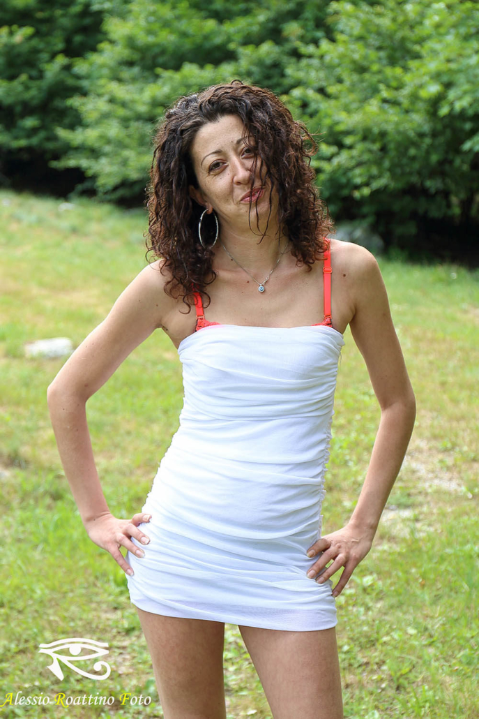Nadia, ragazza con capelli ricci e vestito bianco