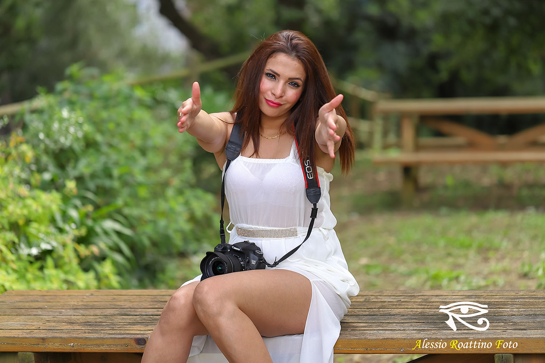 Narjis, ragazza sexy con vestito bianco scosciato, seduta su un tavolino. Ha una reflex canon eos 70d appoggiata sulle gambe e invita a fotografare tendendo le braccia verso chi guarda