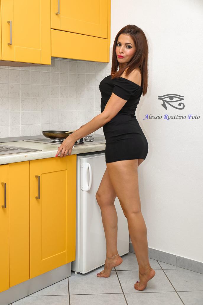 Narjis, ragazza in cucina con abito nero in posa sexy