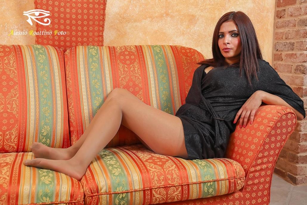 Narjis, ragazza prosperosa in abito nero seduta sul divano