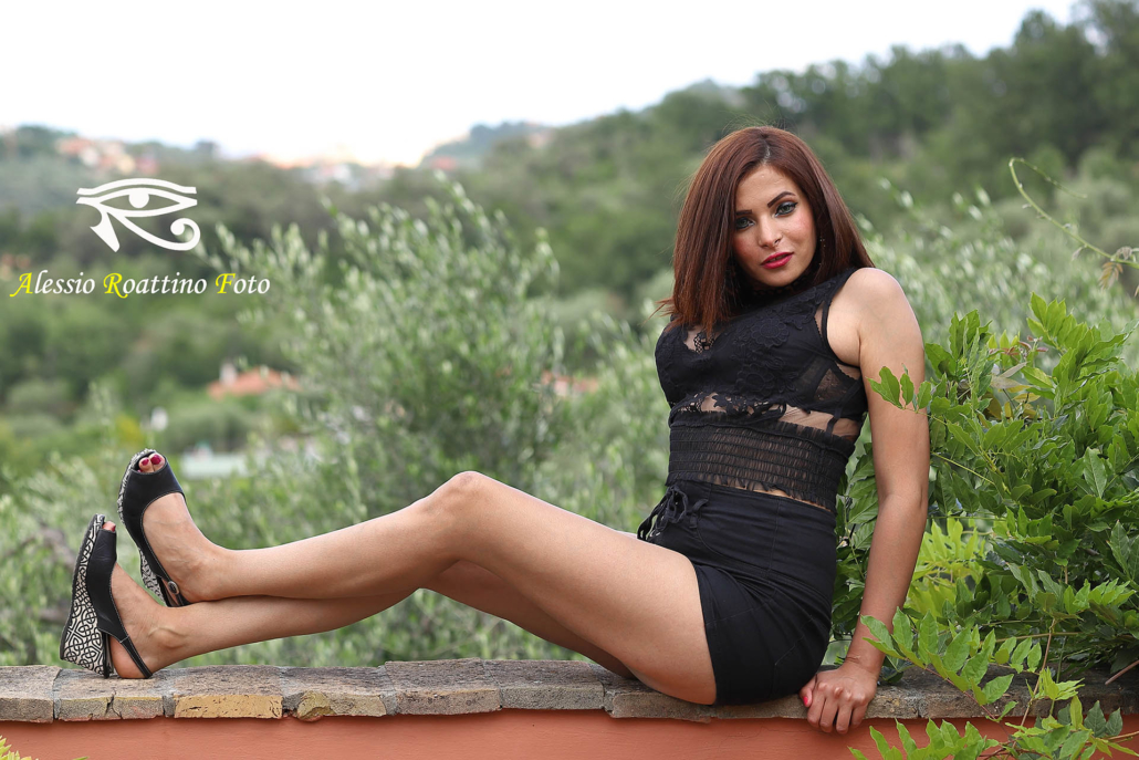 Narjis, modella in abito nero seduta su un muretto vicino a foglie verdi