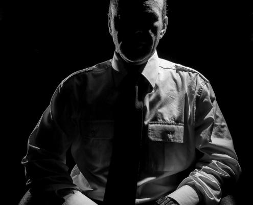 Uomo in camicia ripreso con la tecnica del low key