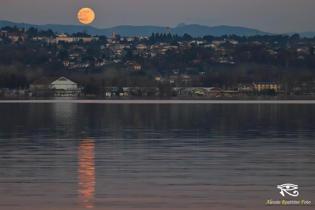 Mentre il sole non è ancora tramontato La luna che sorge da dietro le colline e si specchia nelle acque del lago di Varese