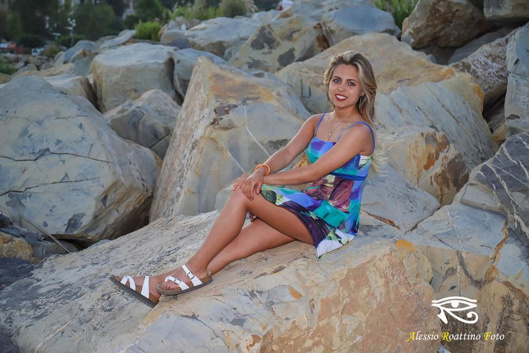 Sharon, bellissima ragazza seduta su uno scoglio a Imperia al tramonto