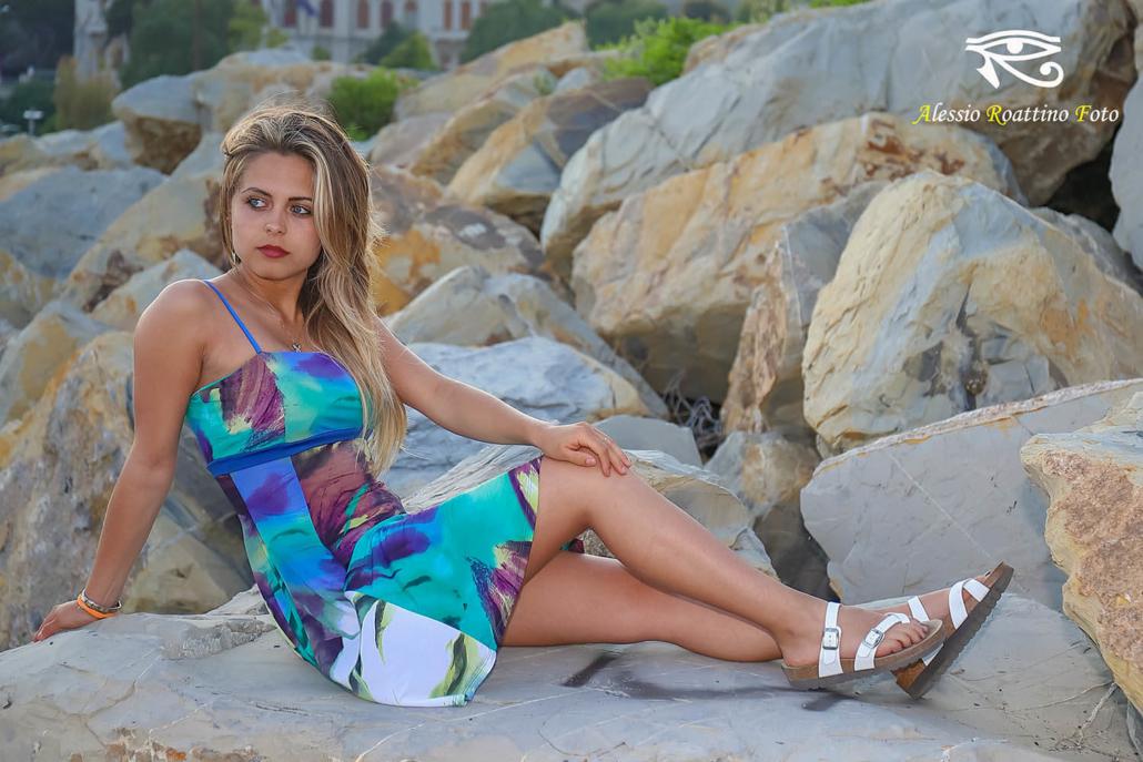 Sharon, bellissima ragazza seduta su uno scoglio a Imperia al tramonto con sguardo assorto