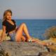 Sharon, modella seduta sugli sogli al tramonto in posa sexy