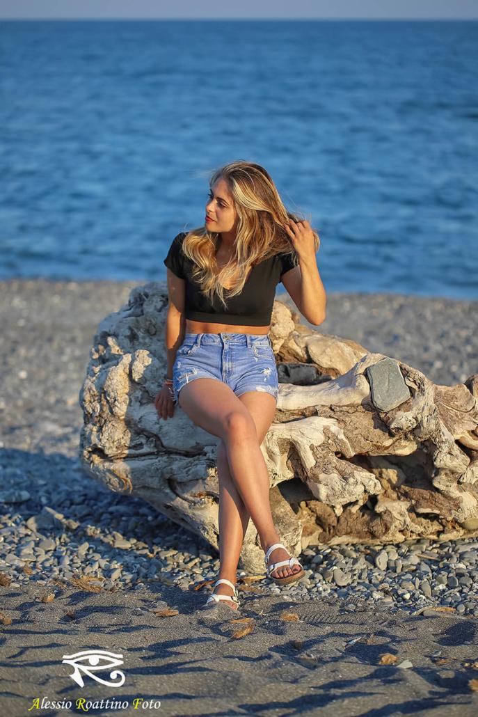 Sharon, modella seduta sul ceppo di un albero sulla spiaggia di Imperia al tramonto