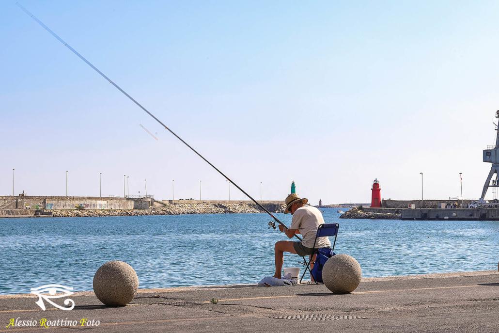 Il pescatore, un uomo seduto su una sedia sulla banchina di Imperia Oneglia con una canna da pesca in mano.